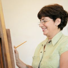 Elderly people painting for hobby. Group of active seniors at art school. Portrait of happy old woman smiling and holding brush.