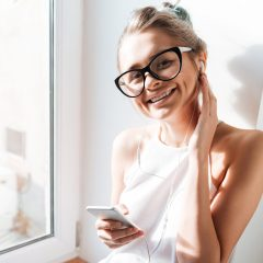 Photo of happy young woman wearing glasses sitting near window at the home listening music. Look at camera.